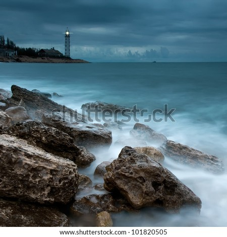Beautiful nightly seascape with lighthouse on the island - stock photo