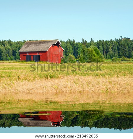 Beautiful nordic red house against the blue sky - stock photo
