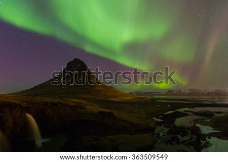 Beautiful northen lights over Kirkjufell mountain in Iceland with fully of star on sky - stock photo