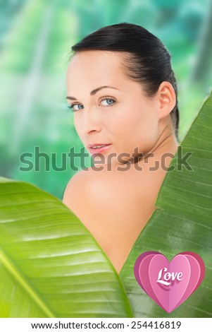 Beautiful nude brunette posing with green leaves against love heart - stock photo