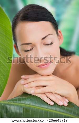 Beautiful nude brunette posing with green leaves on blue and green background