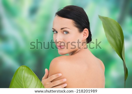 Beautiful nude brunette posing with green leaves on blue and green background - stock photo