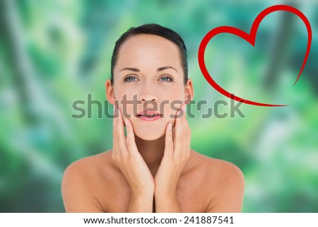 Beautiful nude brunette posing with hands on face against heart - stock photo