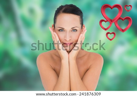 Beautiful nude brunette posing with hands on face against pink hearts - stock photo