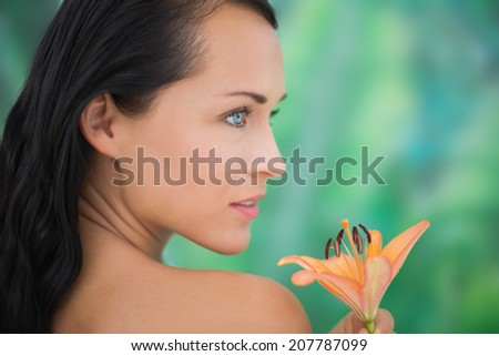 Beautiful nude brunette smelling lily on blue and green background - stock photo