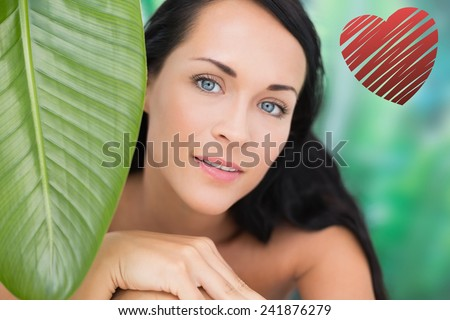 Beautiful nude brunette smiling at camera with green leaf against red heart - stock photo