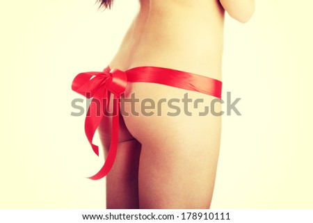 Beautiful nude female as a gift decorated with red ribbon (christmass, birthsday or valentines) - stock photo
