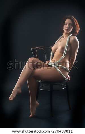 Beautiful nude girl on chair entangled by rope - stock photo
