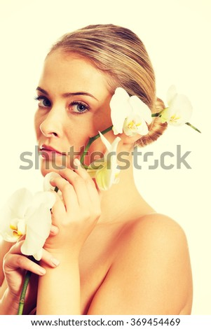 Beautiful nude woman holding white orchid flower - stock photo