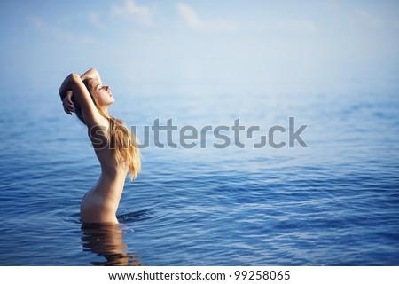 Beautiful nude woman on beach, bali - stock photo