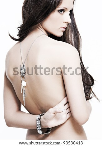 beautiful nude woman with perfect skin and jewelry on a white background - stock photo