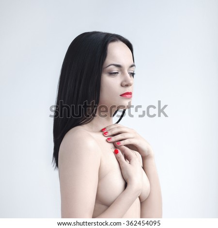 Beautiful nude young sexy woman holding hands over breast. Slim body. Red manicure and lips. - stock photo