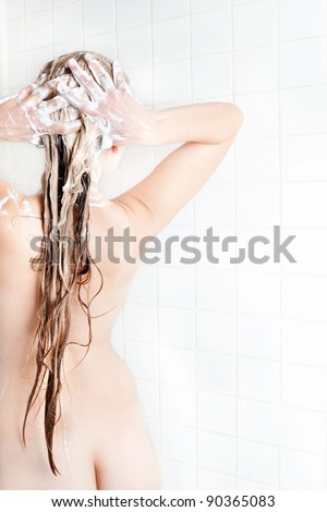 Beautiful nude young woman taking a shower and washing her very long blond hair, rear view on white background - stock photo