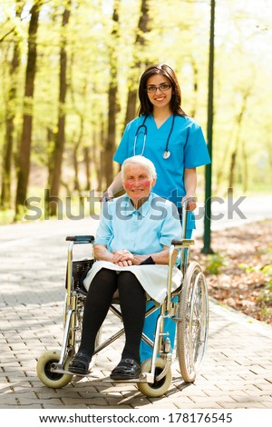 Beautiful nurse and kind elderly lady in wheelchair walking in park together. - stock photo