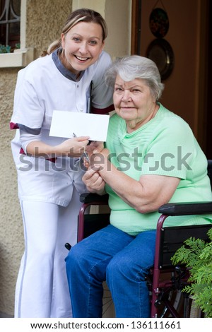 beautiful Nurse and senior patient in a invalid chair gives each other a handshake - stock photo