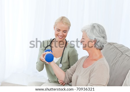 Beautiful nurse helping her patient to do exercises - stock photo
