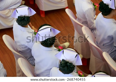 beautiful nurse in white coat and hat with single black stripe. - stock photo