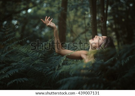 Beautiful nymph resting in a peaceful forest. Romantic and ethereal