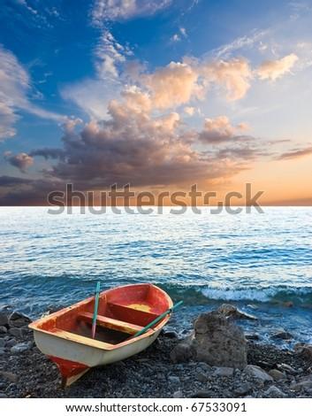 beautiful oared boat on a sea coast at the evening - stock photo