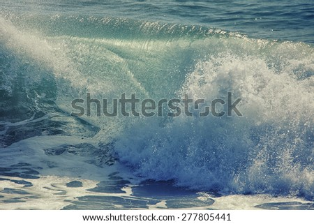 Beautiful ocean wave breaking, abstract background done with a vintage retro instagram filter. - stock photo