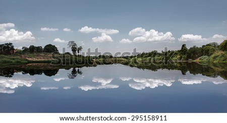 Beautiful of nature - The photo of pastel blue minimal picture with reflection of trees , cloudy sky like a mirror on the water  from countryside of thailand - stock photo