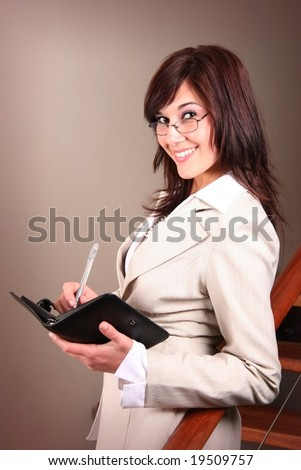 Beautiful office executive writing with a pen in her book
