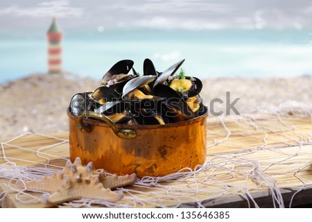 Beautiful old copper pot brimful of cooked mussels standing on old wooden boards covered with a net alongside the coast with a lighthouse visible in the distance - stock photo