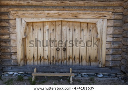 Beautiful old door on the wooden wall of the old house. Lovely rustic background.