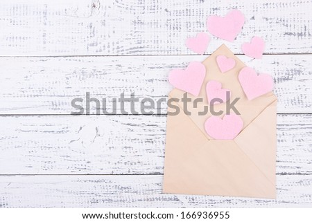 Beautiful old envelope with decorative hearts on wooden background - stock photo