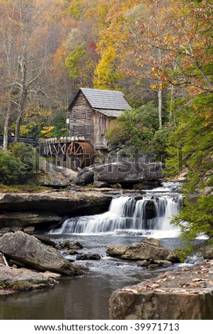 Beautiful old Glade Creek Mill at Babcock State Park in the autumn season also showing the waterfall and mill pond below the mill - stock photo