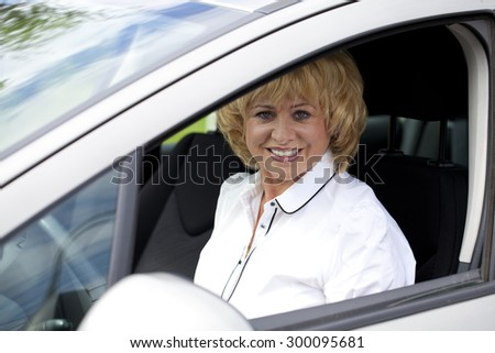 Beautiful old happy elderly driver woman 55-60 years in jacket Driving a Car - stock photo