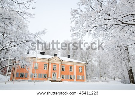 Beautiful old house between snowy trees, Finland