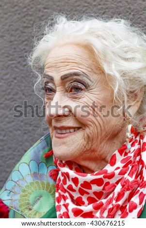 Beautiful old lady. Holiday makeup. Rendezvous, love. Elderly woman fashionably dressed in a park on a bench - stock photo