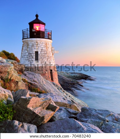Beautiful old lighthouse on rocks at sunset - stock photo