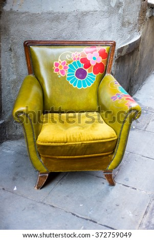 Beautiful old, painted armchairs in the narrow streets of the old part of Barcelona. The piece of furniture is intended as an eye-catcher for tourists and buyers in the La Ribera district of Barcelona - stock photo