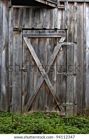Beautiful old rustic wooden barn door with green weeds growing at the base - stock photo