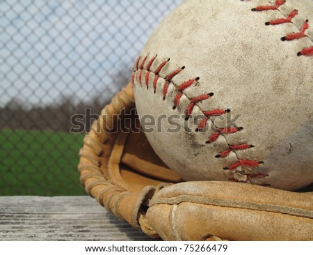 Beautiful old softball with shallow depth of field in a vintage mitt on the sidelines - stock photo