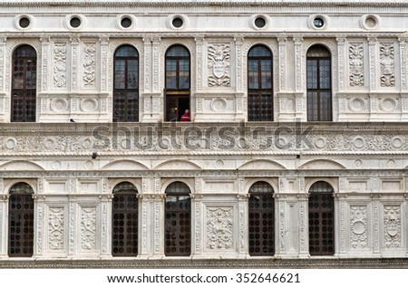 Beautiful old white facade at a historic building with stone carvings and decorations - stock photo