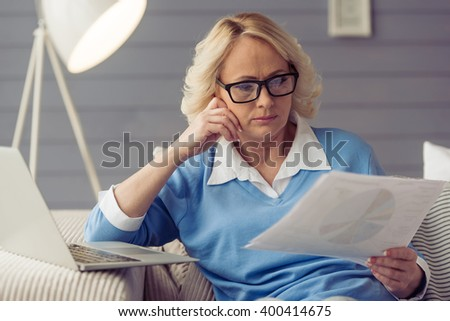 Beautiful old woman in casual clothes and glasses is holding papers while working with laptop at home
