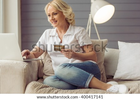 Beautiful old woman in casual clothes is holding a credit card, using a laptop and smiling while sitting in armchair at home - stock photo