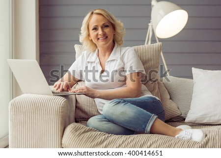 Beautiful old woman in casual clothes is using a laptop, looking at camera and smiling while sitting on couch at home