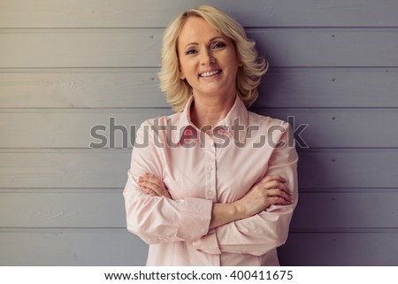 Beautiful old woman in classic shirt is looking at camera and smiling, standing with crossed arms against gray wooden background - stock photo