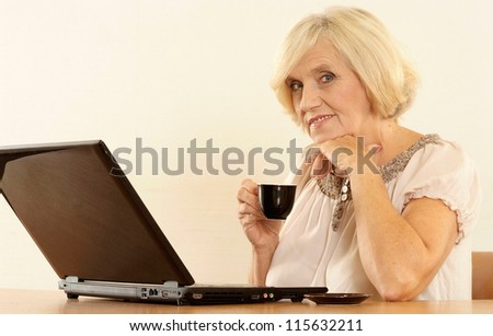 beautiful old woman with a laptop on a beige - stock photo