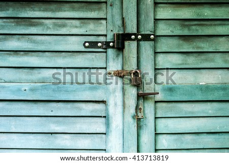 Beautiful old wooden garage plank door with faded paint - stock photo