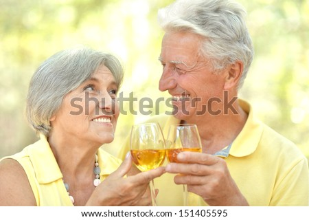 Beautiful older couple drinking wine - stock photo
