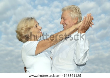 beautiful older couple  on the background of sky - stock photo
