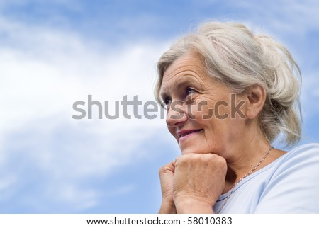 beautiful older woman stands on the sky - stock photo
