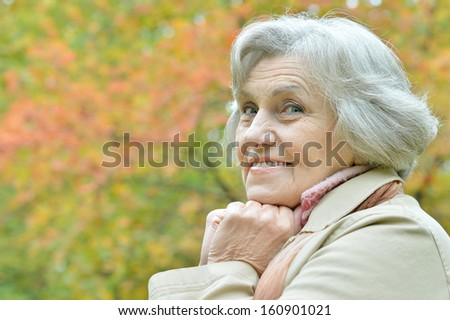 beautiful older woman walking in the park in September