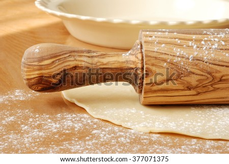 Beautiful olive wood rolling pin with flour dusted pastry dough and empty ceramic pie dish.  Closeup with natural light and shallow dof.  Baking concept. - stock photo