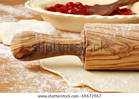 Beautiful olive wood rolling pin with homemade pie crust and cherry filling.  Macro with shallow dof. - stock photo